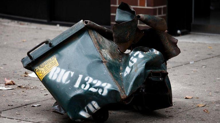 A mangled dumpster sits on the sidewalk on