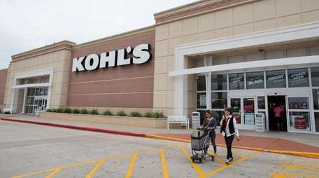 Shoppers push a cart of items as they