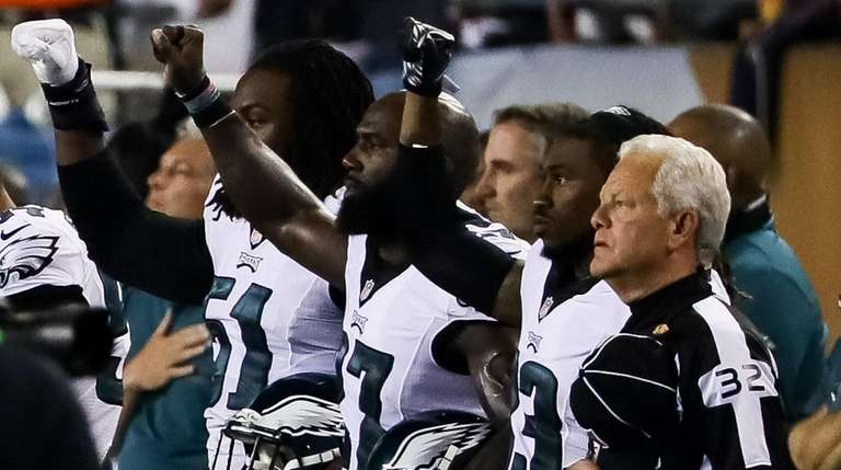 Philadelphia Eagles players hold up their right fists