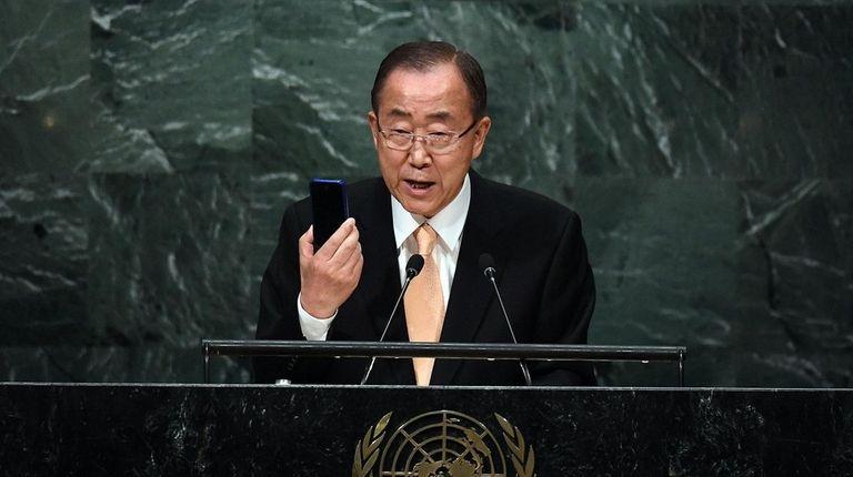 United Nations Secretary-General Ban Ki-moon holds up a