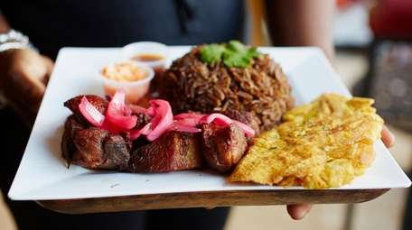 Griot dressed with pickled red onions comes with
