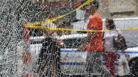 New Yorkers pass a shattered storefront window on
