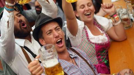 Visitors hold up one-liter glasses of beer to