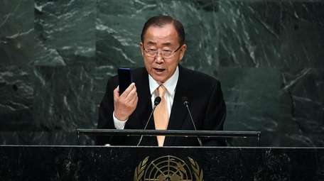 United Nations Secretary-General Ban Ki-moon holds up a
