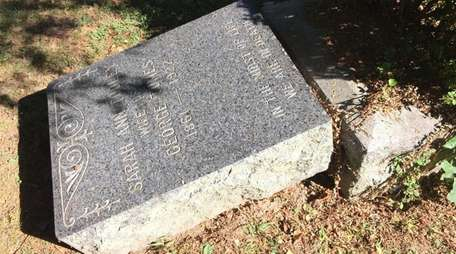 Vandals toppled about two dozen tombstones, including this