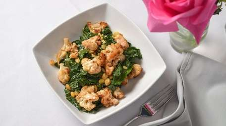 Roasted cauliflower joins kale, pignoli and golden raisins