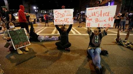 Demonstrators sit on a street during a protest