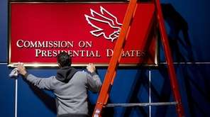 A worker cleans a sign for the Commission