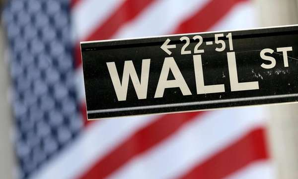A Wall Street street sign is framed by