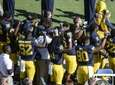 Michigan football players raise their fists up in