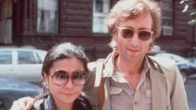 John Lennon and his wife, Yoko Ono, walk