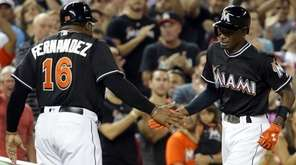 Miami Marlins' Dee Gordon, right, shakes hands with