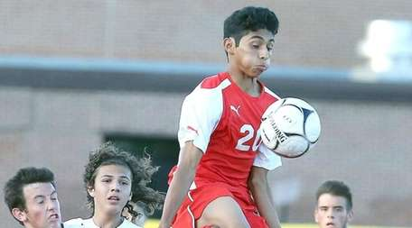 Mineola's Christian Melendez leaps high to control the