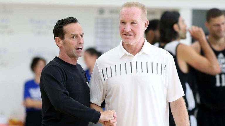 St. John's coach Chris Mullin, right,talks to Nets