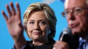 Democratic presidential candidate Hillary Clinton listens as Sen.