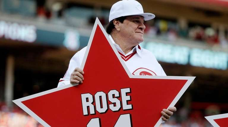 Former Cincinnati Reds player Pete Rose holds his