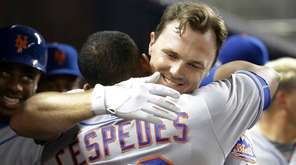 New York Mets' Jay Bruce, right, hugs Yoenis