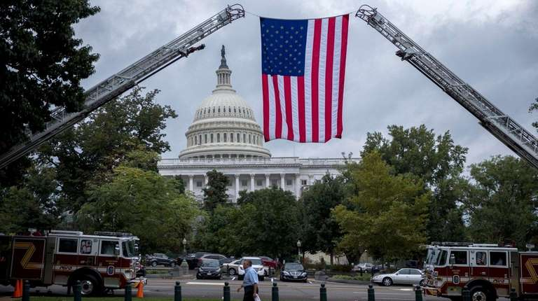 An American flag is suspended from fire department