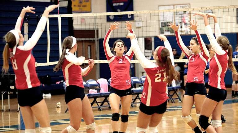 The Smithtown East girls volleyball team celebrates a