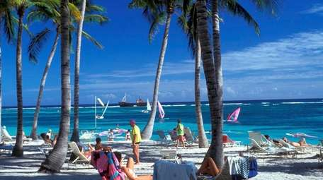Vacationers lounge on the beach at Club Med