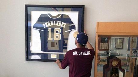 Alonso High School custodian Matt Stuewe hangs the