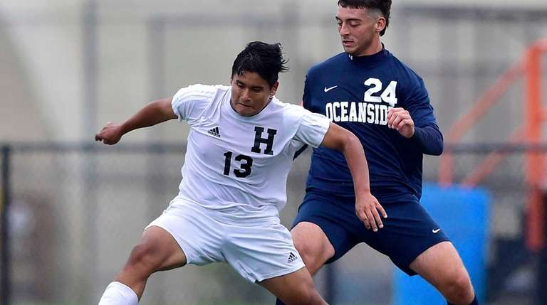 Hicksville's John Rojas, left, is defended by Oceanside's