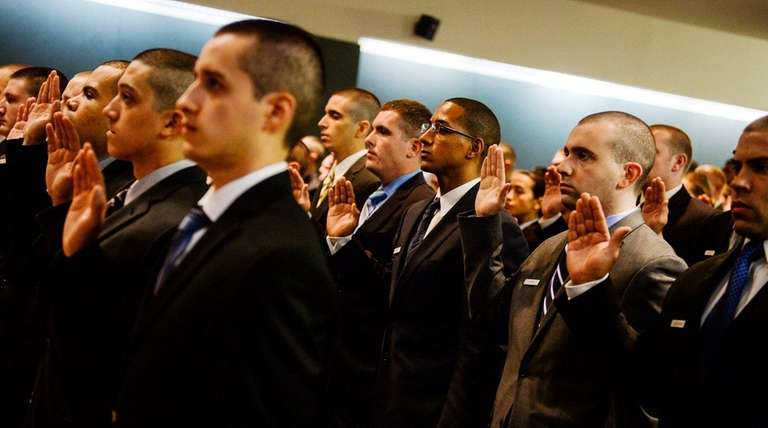 Suffolk County police recruits take the oath during