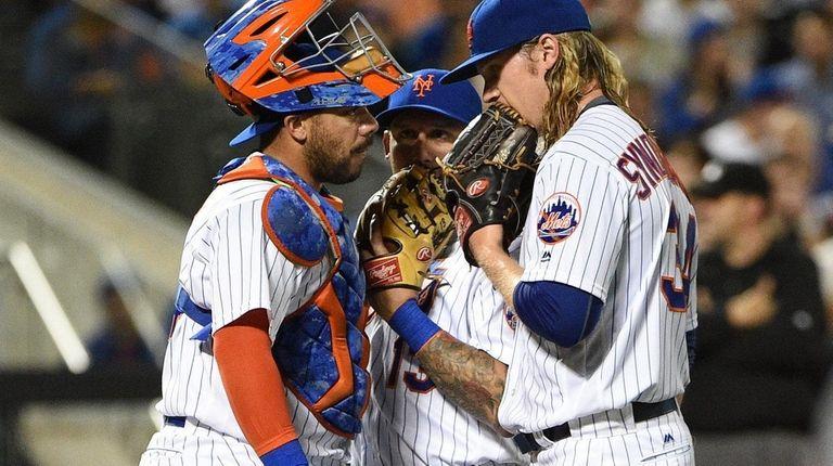 Mets catcher Rene Rivera, left, huddles with shortstop