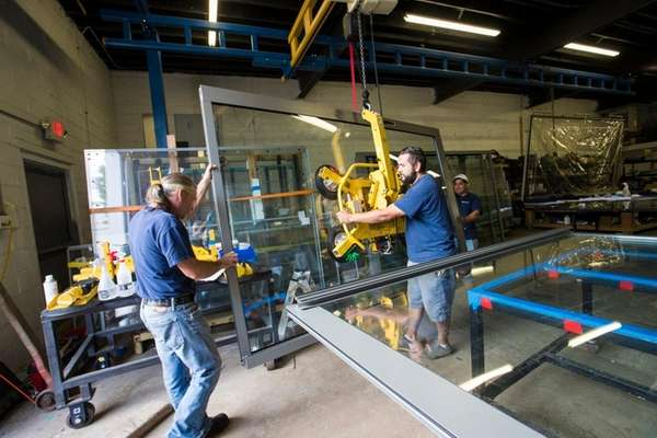 Westhampton Architectural Glass Inc. workers move a glass