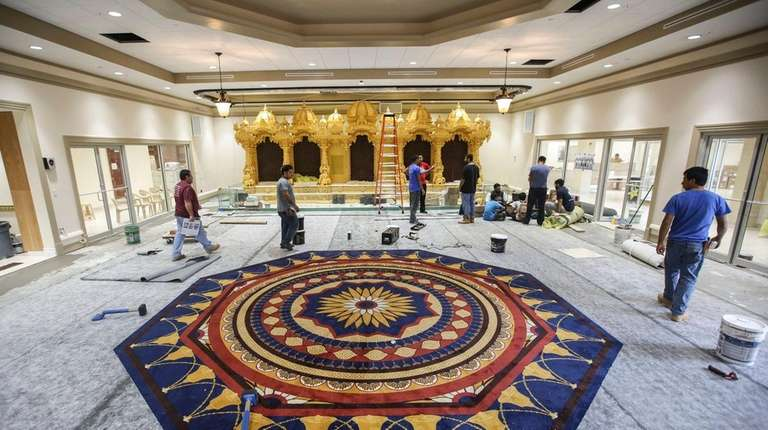 Workers put finishing touches inside the sanctuary of