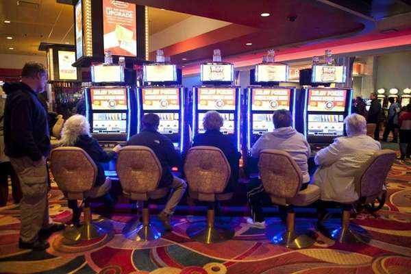 Guests play slot machines at Resorts World Casino
