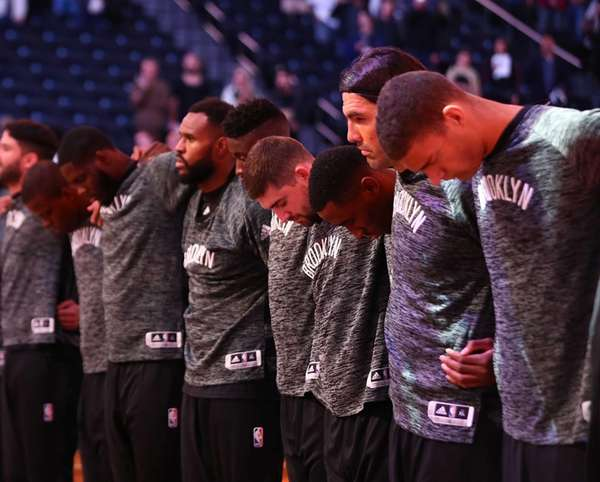 Members of the Brooklyn Nets stand before the