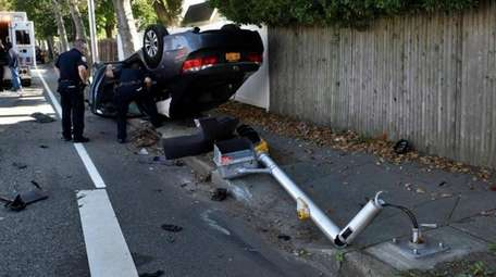 An overturned vehicle sits on a sidewalk along