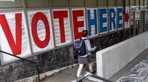 A voter passes a large sign before voting