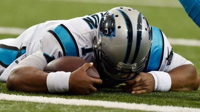 Carolina Panthers' quarterback Cam Newton lies on the