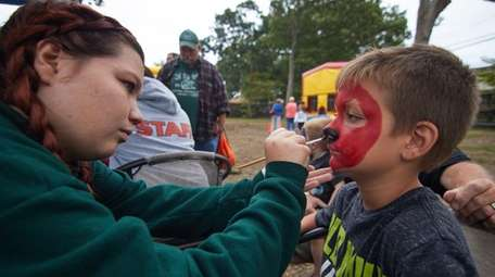 Ryan Rossiter, 9, gets his face painted by