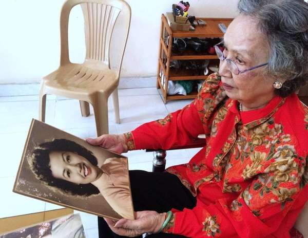 Trinh Thi Ngo holds a portrait of her