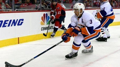 Islanders defenseman Travis Hamonic moves the puck against