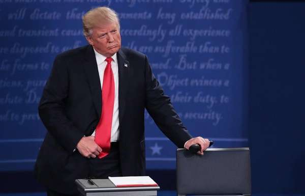 Republican presidential nominee Donald Trump listens during the