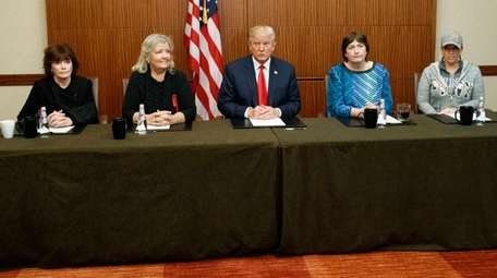 Republican presidential candidate Donald Trump, center, sits with,