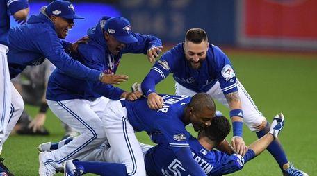 Toronto Blue Jays players mob Russell Martin (bottom)