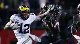 Michigan running back Chris Evans (12) fights off