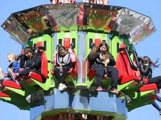Festivalgoers enjoy the Super Shot ride during the