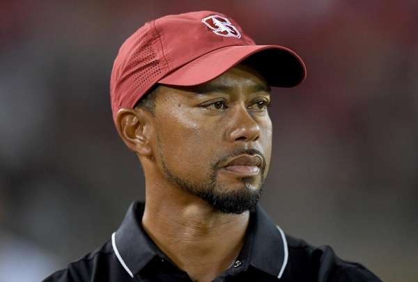 Tiger Woods looks on from the sidelines during