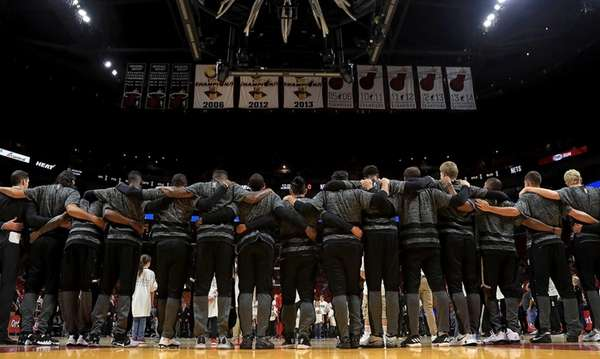 The Brooklyn Nets stand arm in arm during
