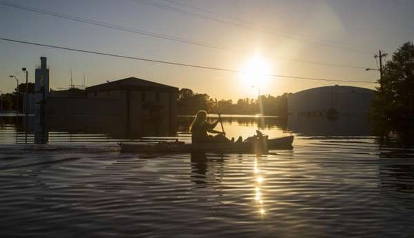 Buckley Miller paddles a canoe past a flooded