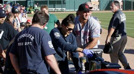 Scottsdale Scorpions outfielder Tim Tebow, center, comforts a