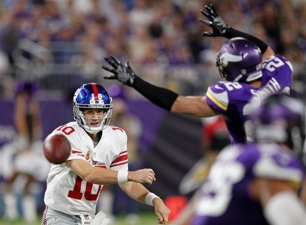 New York Giants quarterback Eli Manning, left, throws