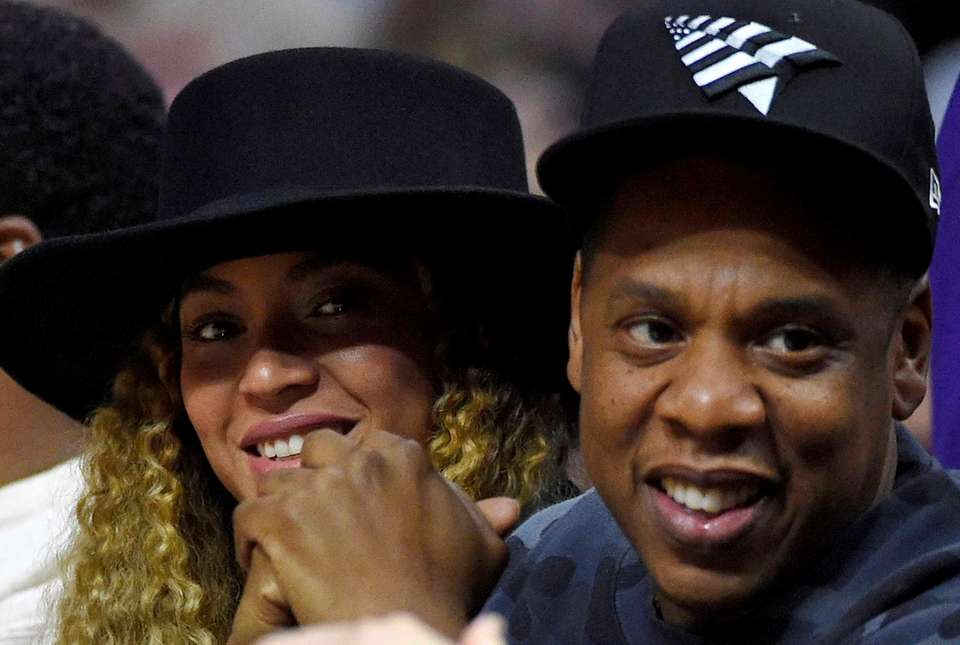 Singers Beyonce and Jay Z watch during the