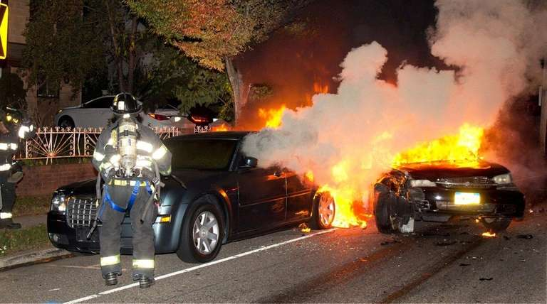 Firefighters work to extinguish a three-car crash on